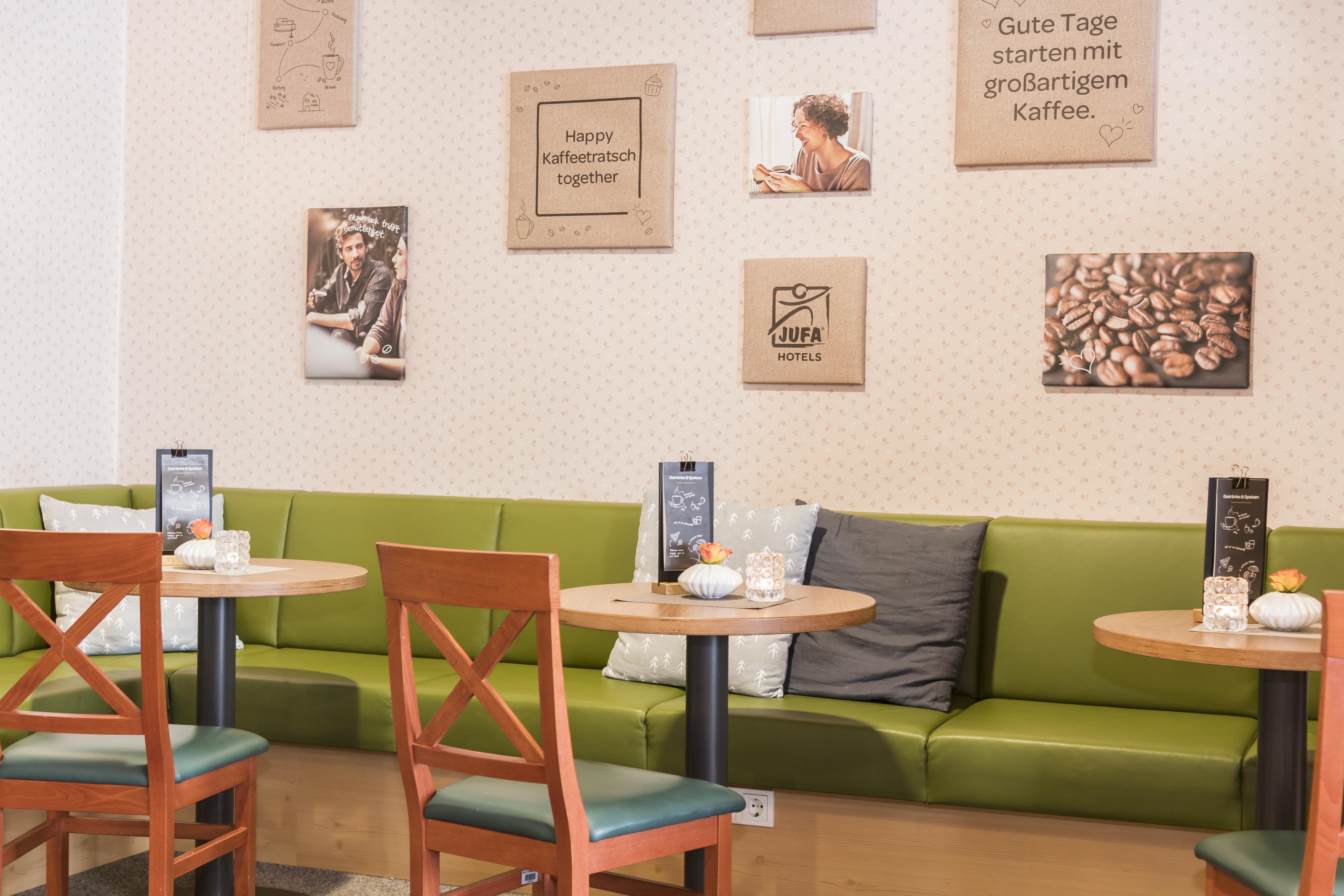 Sie sehen das gemütliche Café im JUFA Hotel Grundlsee*** mit Wandbildern. JUFA Hotels bietet erholsamen Familienurlaub und einen unvergesslichen Winterurlaub.
