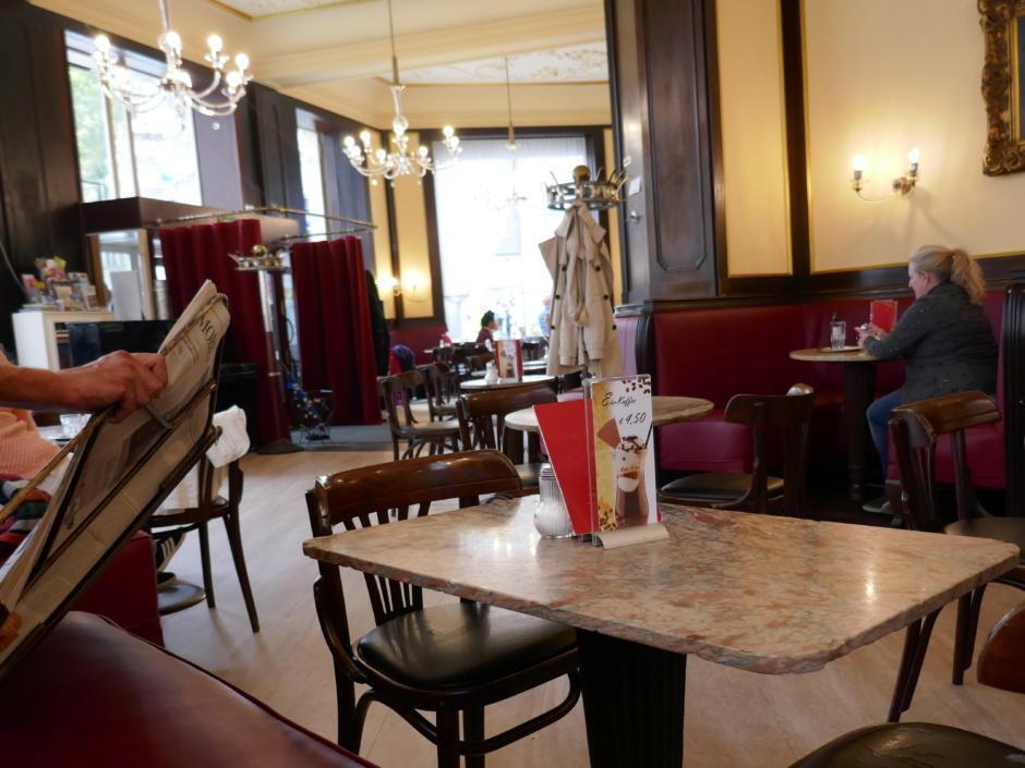 Sie sehen ein Café in Wien mit Kronleuchtern. JUFA Hotels bietet erholsamen Familienurlaub und einen unvergesslichen Winterurlaub.