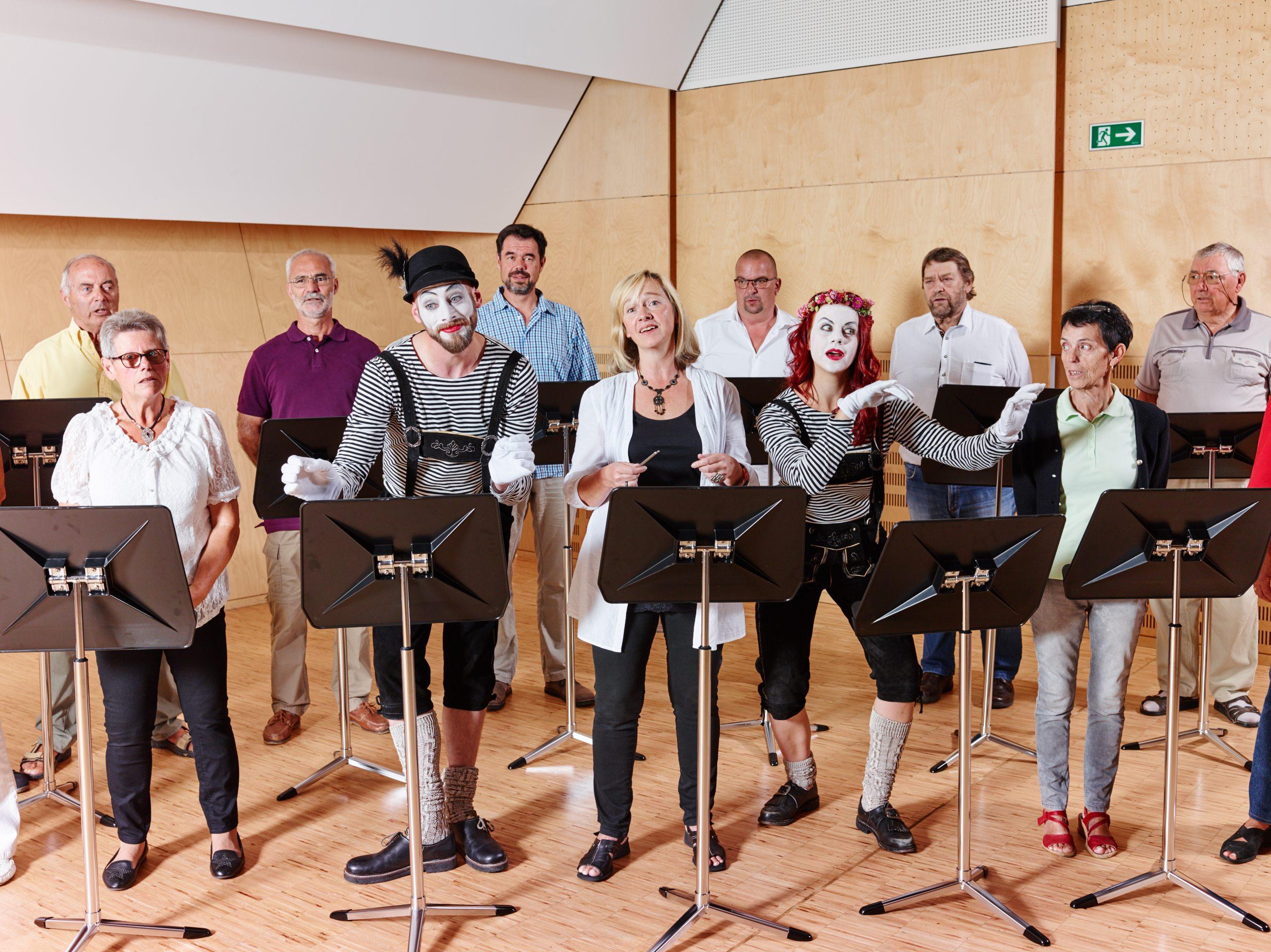 Sie sehen einen Chor in der Musikakademie Knappenberg mit Pantomimen. JUFA Hotels bietet den idealen Platz zum Musizieren und Singen in der Gemeinschaft in abwechslungsreichen Regionen.