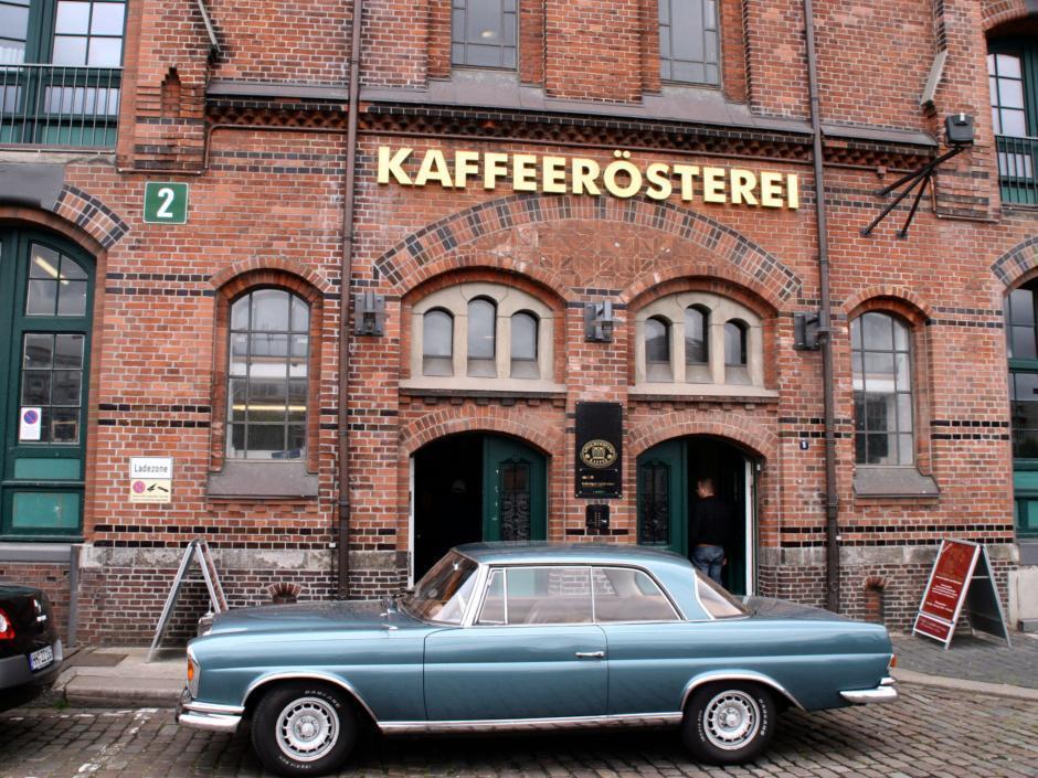 JUFA Hotel Hamburg HafenCity Genusstour Hamburg. Ein altes Gebäude mit einem Oldtimer vor der Haustür. Genusstour durch Hamburg mit Stopp bei einer Kafferösterei.