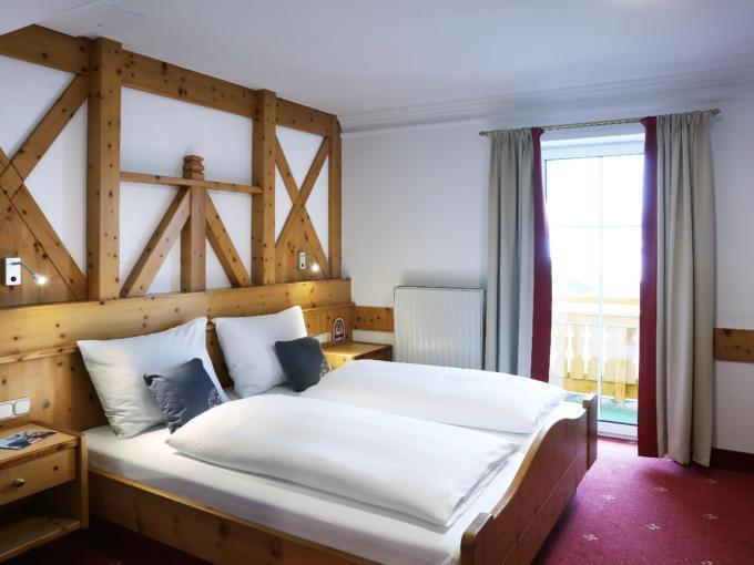 Sie sehen ein Doppelbett in einem Doppelzimmer im JUFA Alpenhotel Saalbach**** mit Balkonfenster. JUFA Hotels bietet erholsamen Familienurlaub und einen unvergesslichen Winterurlaub.