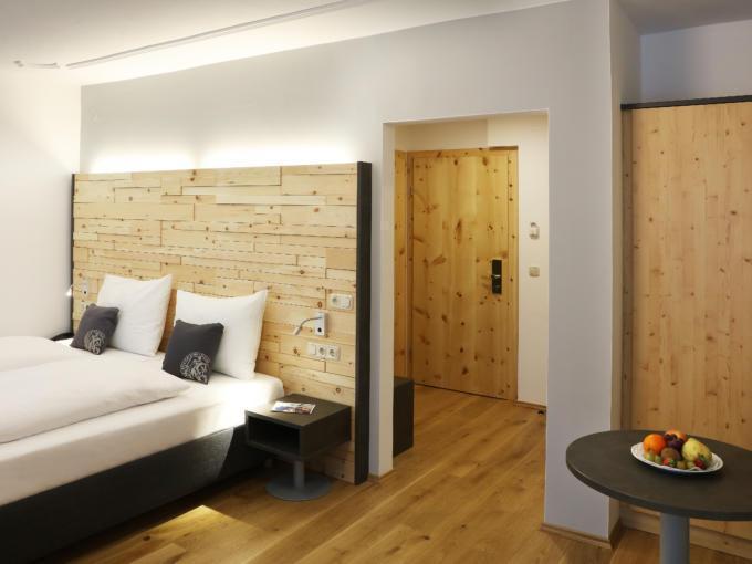 Sie sehen ein Doppelbett in einem Doppelzimmer im JUFA Alpenhotel Saalbach**** mit Obstschale. JUFA Hotels bietet erholsamen Familienurlaub und einen unvergesslichen Winterurlaub.