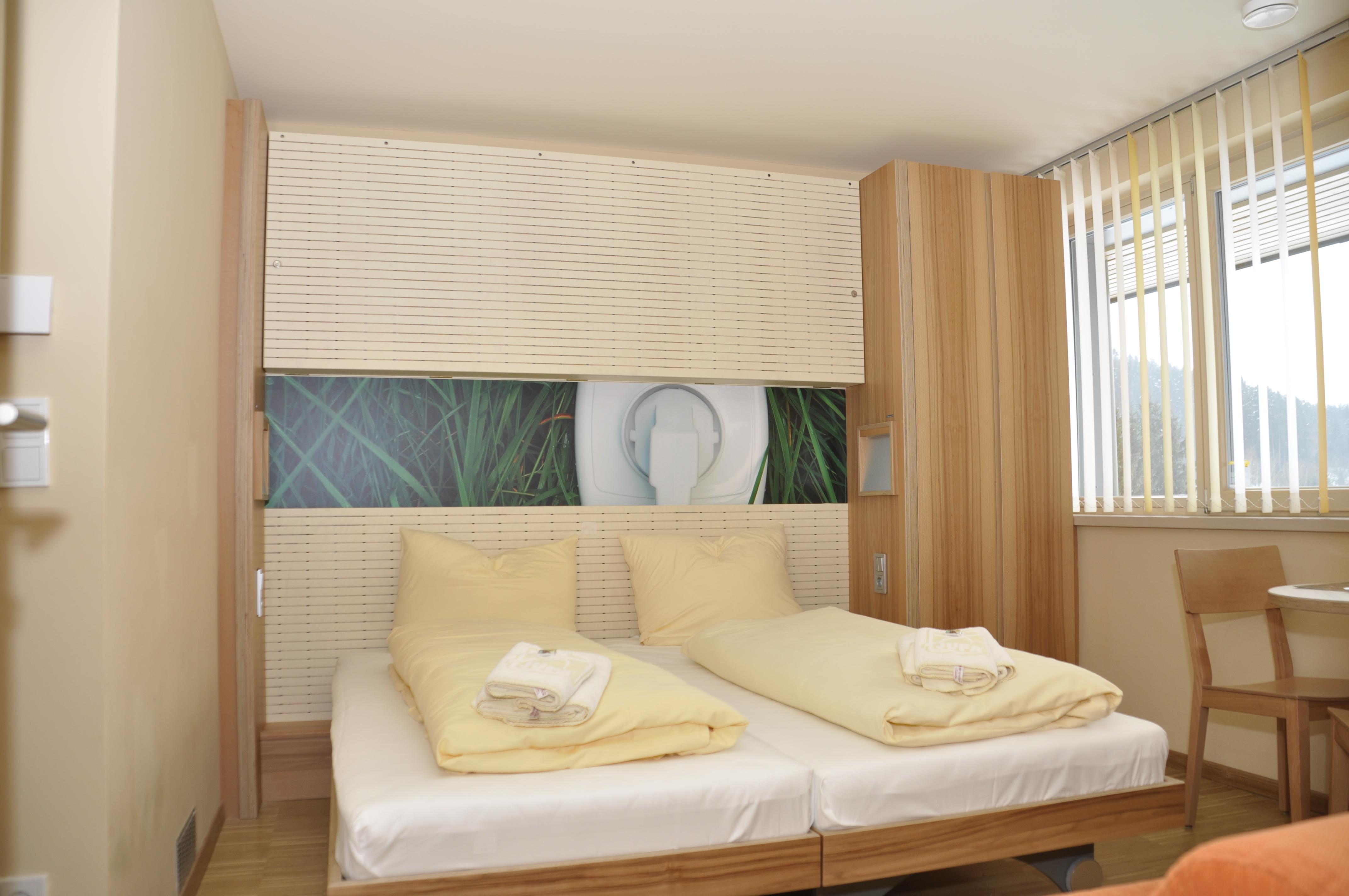 Sie sehen ein Doppelbett in einem Doppelzimmer im JUFA Hotel Bleiburg/Pliberk – Sport-Resort mit einem Wandbild. JUFA Hotels bietet Ihnen den Ort für erfolgreiches Training in ungezwungener Atmosphäre für Vereine und Teams.
