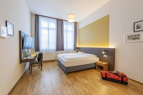Sie sehen ein Doppelbett in einem Doppelzimmer im JUFA Hotel Bregenz mit TV. JUFA Hotels bietet erlebnisreichen Städtetrip für die ganze Familie und den idealen Platz für Ihr Seminar.