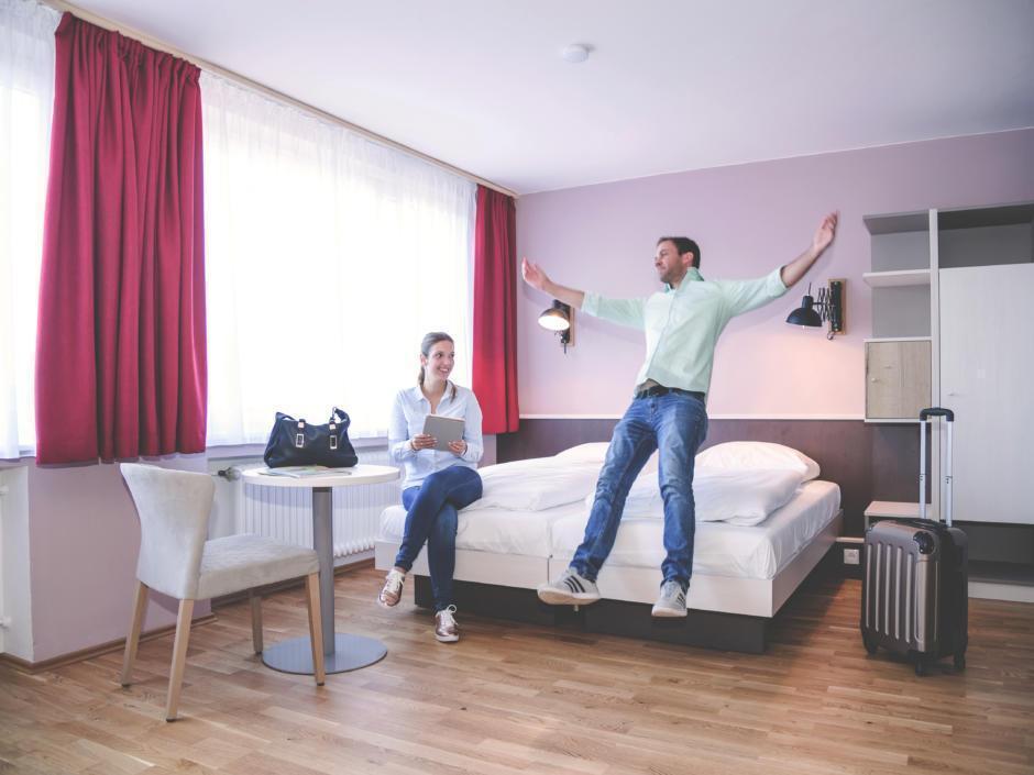 Sie sehen ein Doppelbett in einem Doppelzimmer im JUFA Hotel Königswinter/Bonn mit Gästen. JUFA Hotels bietet erlebnisreichen Städtetrip für die ganze Familie und den idealen Platz für Ihr Seminar.