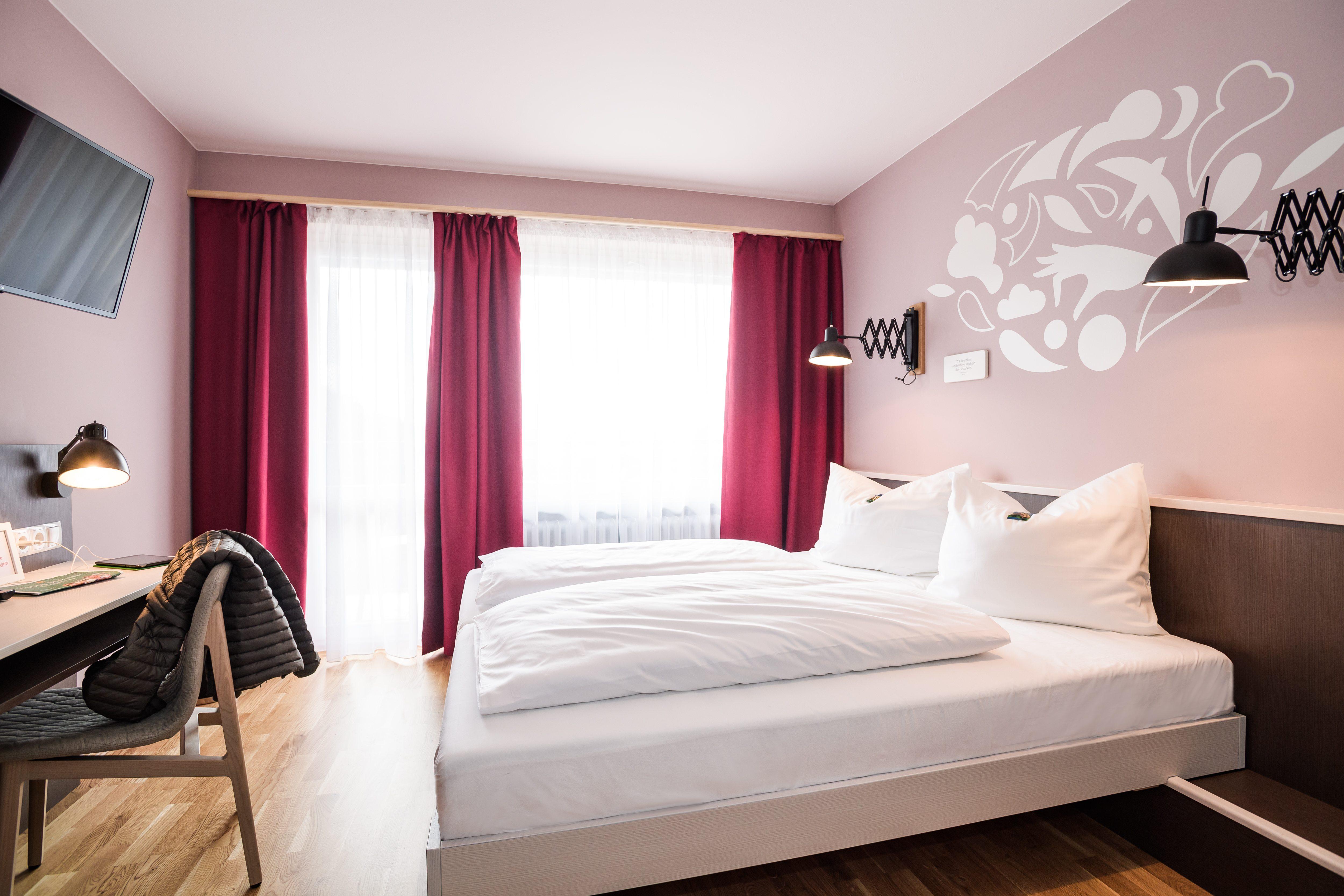 Sie sehen ein Doppelbett in einem Doppelzimmer im JUFA Hotel Königswinter mit Fernseher. JUFA Hotels bietet erlebnisreichen Städtetrip für die ganze Familie und den idealen Platz für Ihr Seminar.