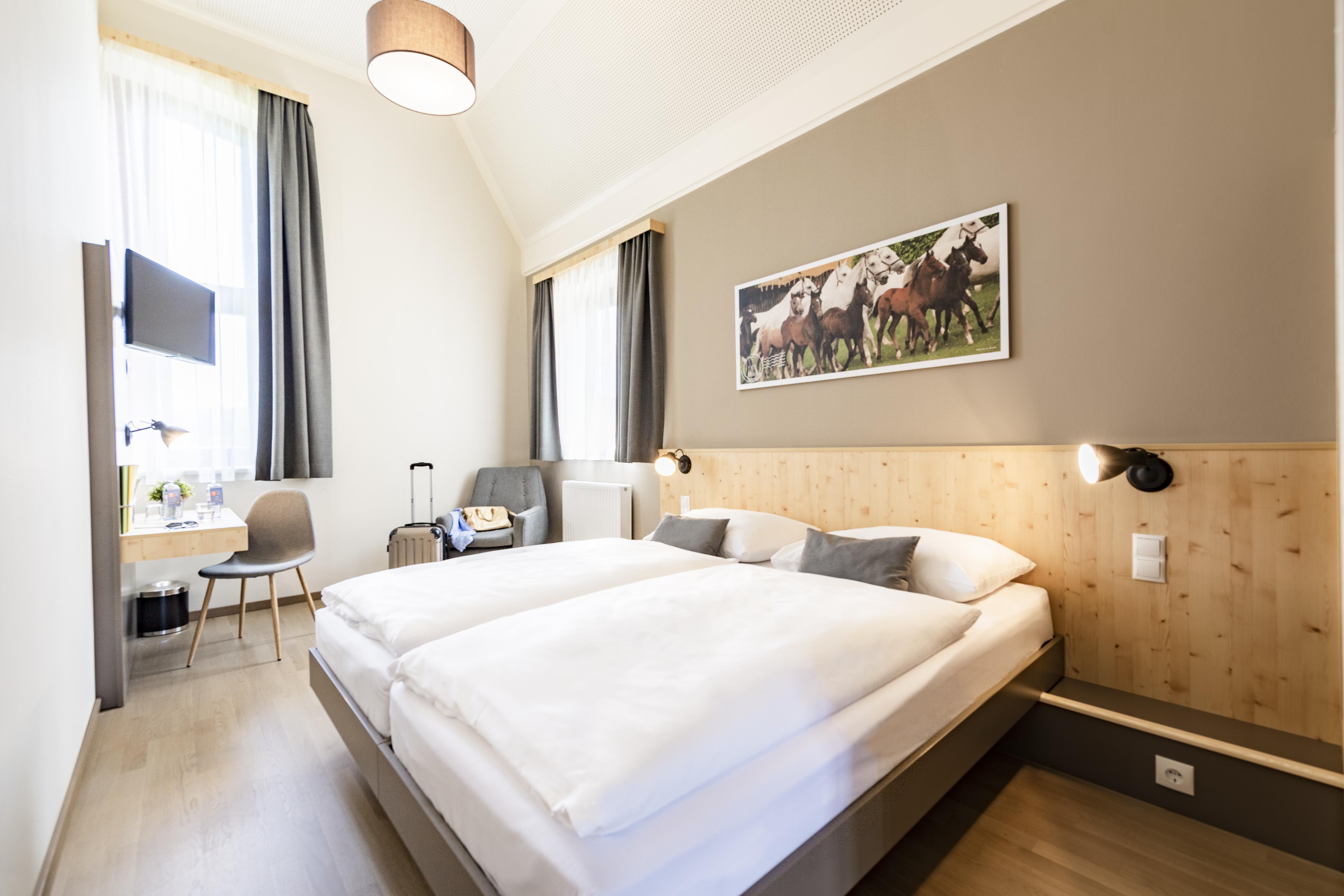 Sie sehen ein Doppelbett in einem Doppelzimmer im JUFA Hotel Maria Lankowitz mit Fernseher. JUFA Hotels bietet tollen Sommerurlaub an schönen Seen für die ganze Familie.