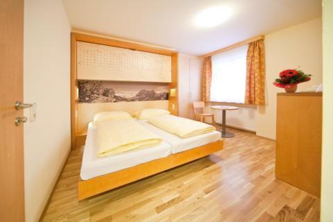 Sie sehen ein Doppelbett in einem Doppelzimmer im JUFA Hotel Montafon mit einem Wandbild. JUFA Hotels bietet erholsamen Familienurlaub und einen unvergesslichen Winter- und Wanderurlaub.
