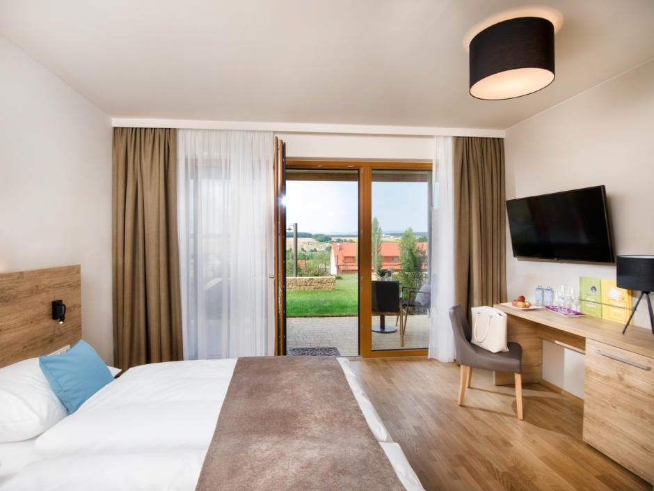 Sie sehen ein Doppelbett in einem Doppelzimmer Plus im JUFA Hotel Neutal – Landerlebnis mit Terrasse. JUFA Hotels bietet Ihnen den Ort für erlebnisreichen Natururlaub für die ganze Familie.