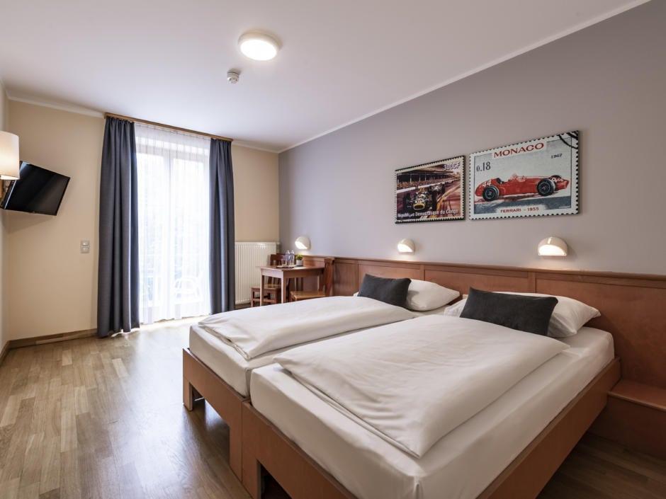Sie sehen ein Doppelbett in einem Doppelzimmer im JUFA Hotel Seckau mit Wandbildern. JUFA Hotels bietet erholsamen Familienurlaub und einen unvergesslichen Winter- und Wanderurlaub.