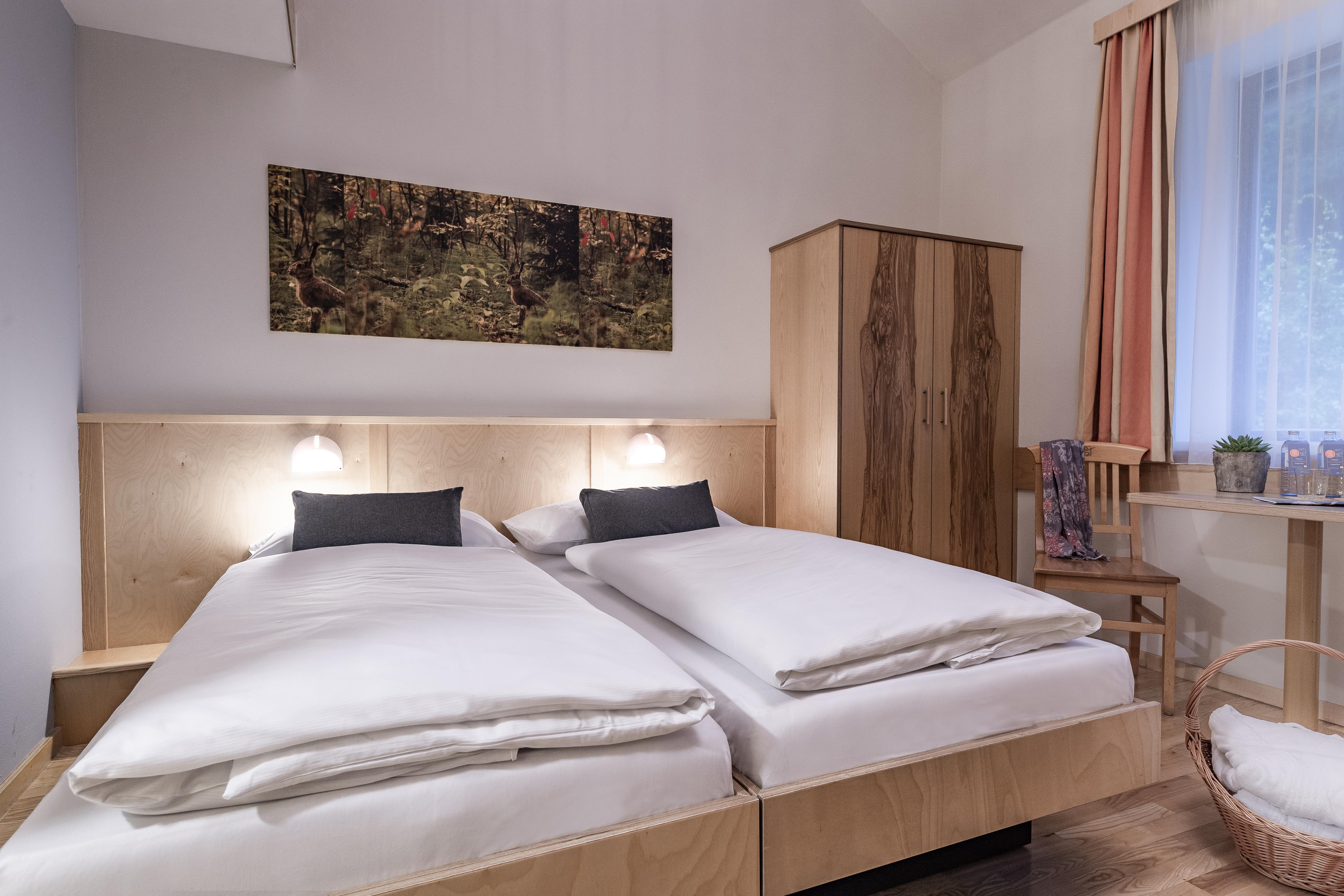 Sie sehen ein Doppelbett in einem Doppelzimmer im JUFA Natur-Hotel Bruck mit Wandbild. JUFA Hotels bietet Ihnen den Ort für erlebnisreichen Natururlaub für die ganze Familie.