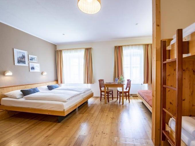 Sie sehen ein Doppelbett in einem Familienzimmer Typ Family and Friends 5 im JUFA Hotel Murau mit Tisch. JUFA Hotels bietet erholsamen Familienurlaub und einen unvergesslichen Winter- und Wanderurlaub.
