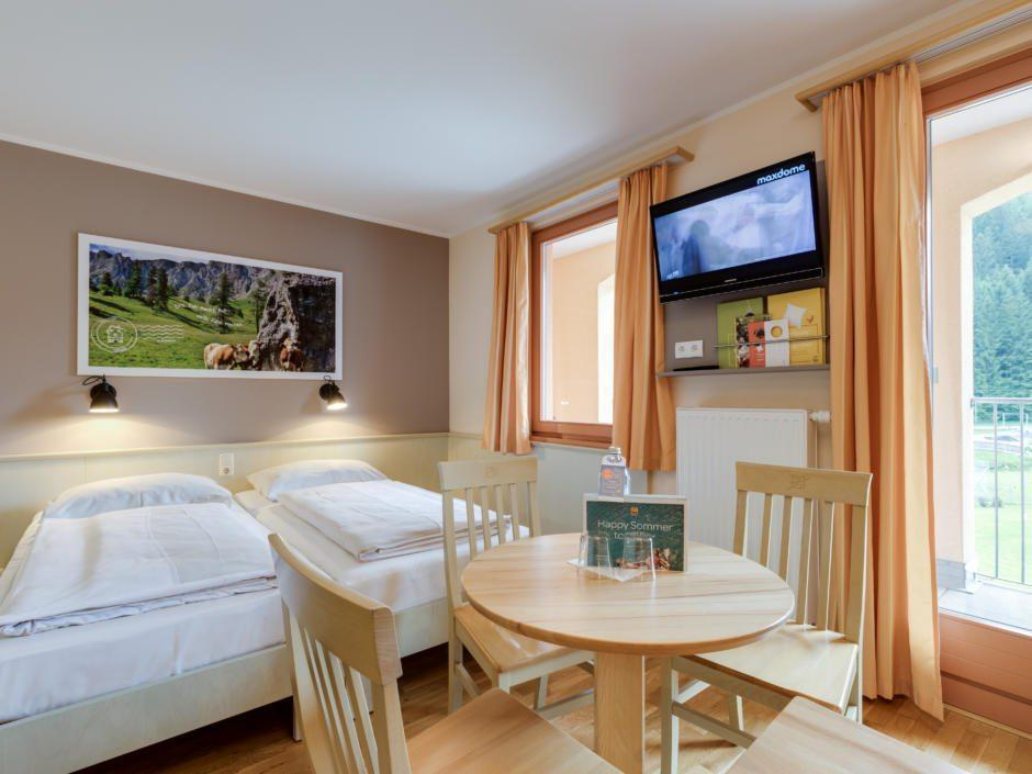 Sie sehen ein Doppelbett im Familienzimmer im JUFA Hotel Veitsch. Der Ort für kinderfreundlichen und erlebnisreichen Urlaub für die ganze Familie.