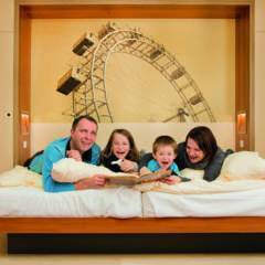 Sie sehen ein Doppelbett in einem Familienzimmer large im JUFA Hotel Wien City mit einer Familie. JUFA Hotels bietet erholsamen Familienurlaub und einen unvergesslichen Winter- und Wanderurlaub.