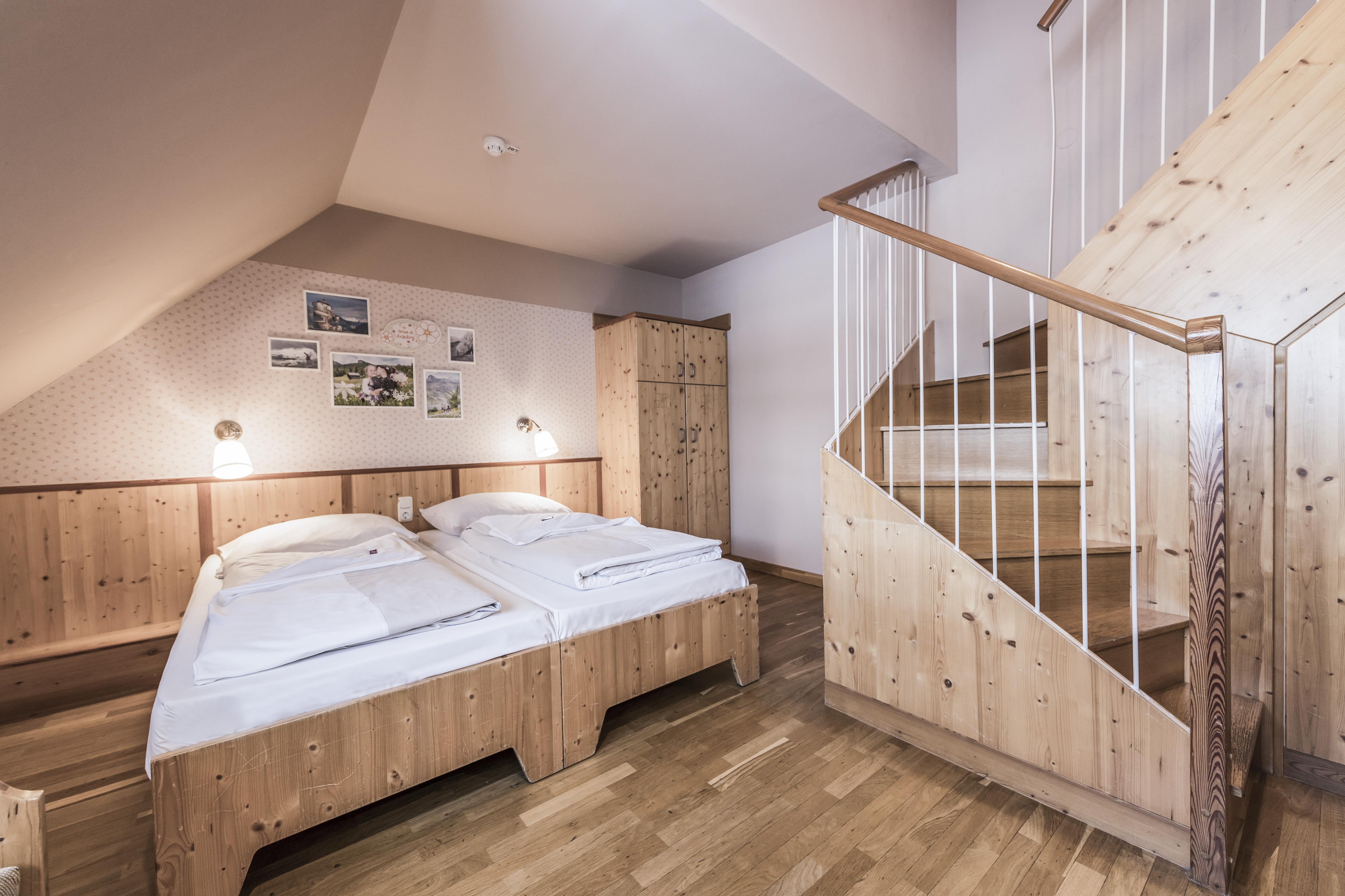 Sie sehen ein Doppelbett in einem Galeriezimmer large im JUFA Hotel Grundlsee*** mit einer Treppe. JUFA Hotels bietet erholsamen Familienurlaub und einen unvergesslichen Winter- und Wanderurlaub.