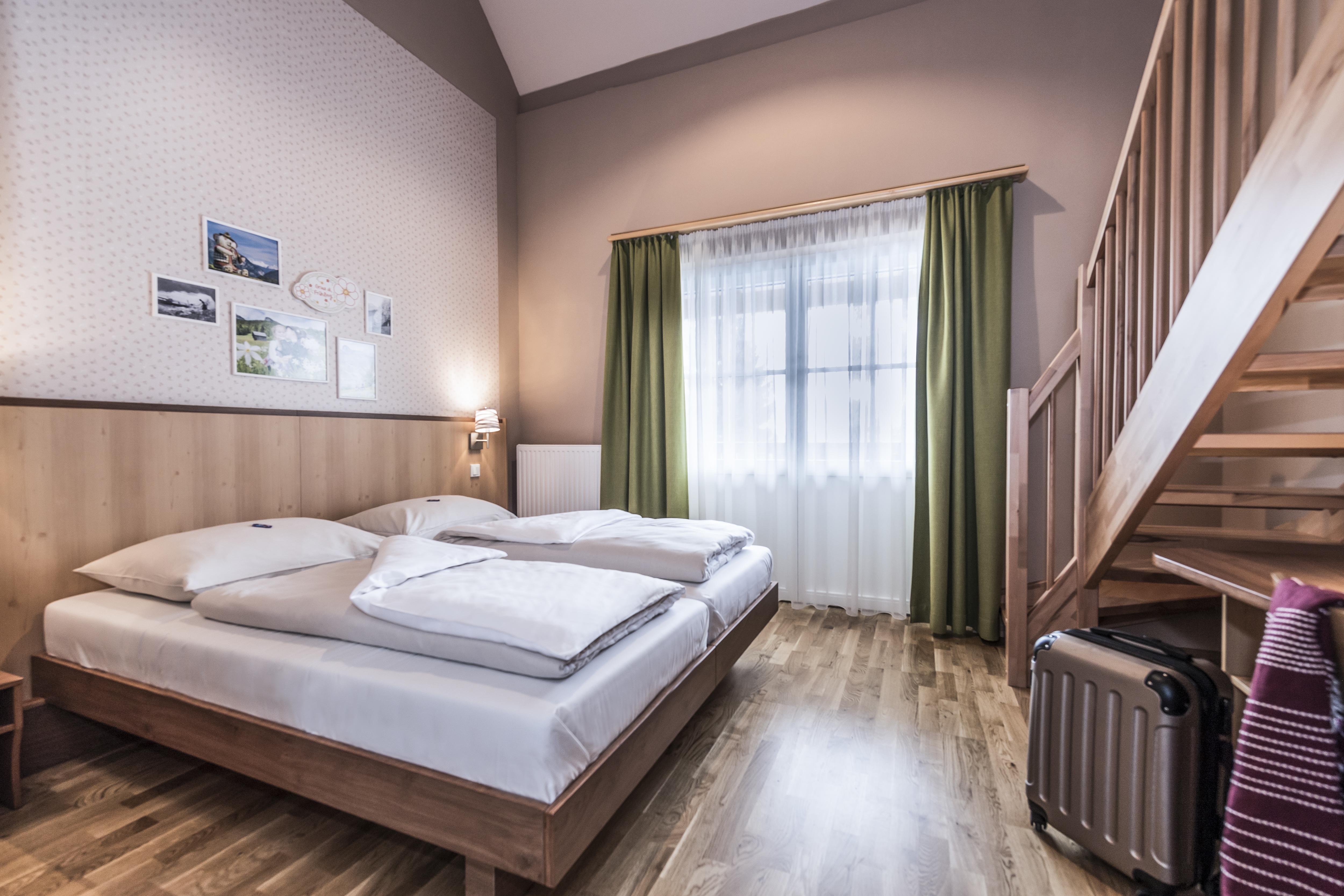 Sie sehen ein Doppelbett in einem Galeriezimmer Plus im JUFA Hotel Grundlsee*** mit einem Koffer. JUFA Hotels bietet erholsamen Familienurlaub und einen unvergesslichen Winter- und Wanderurlaub.