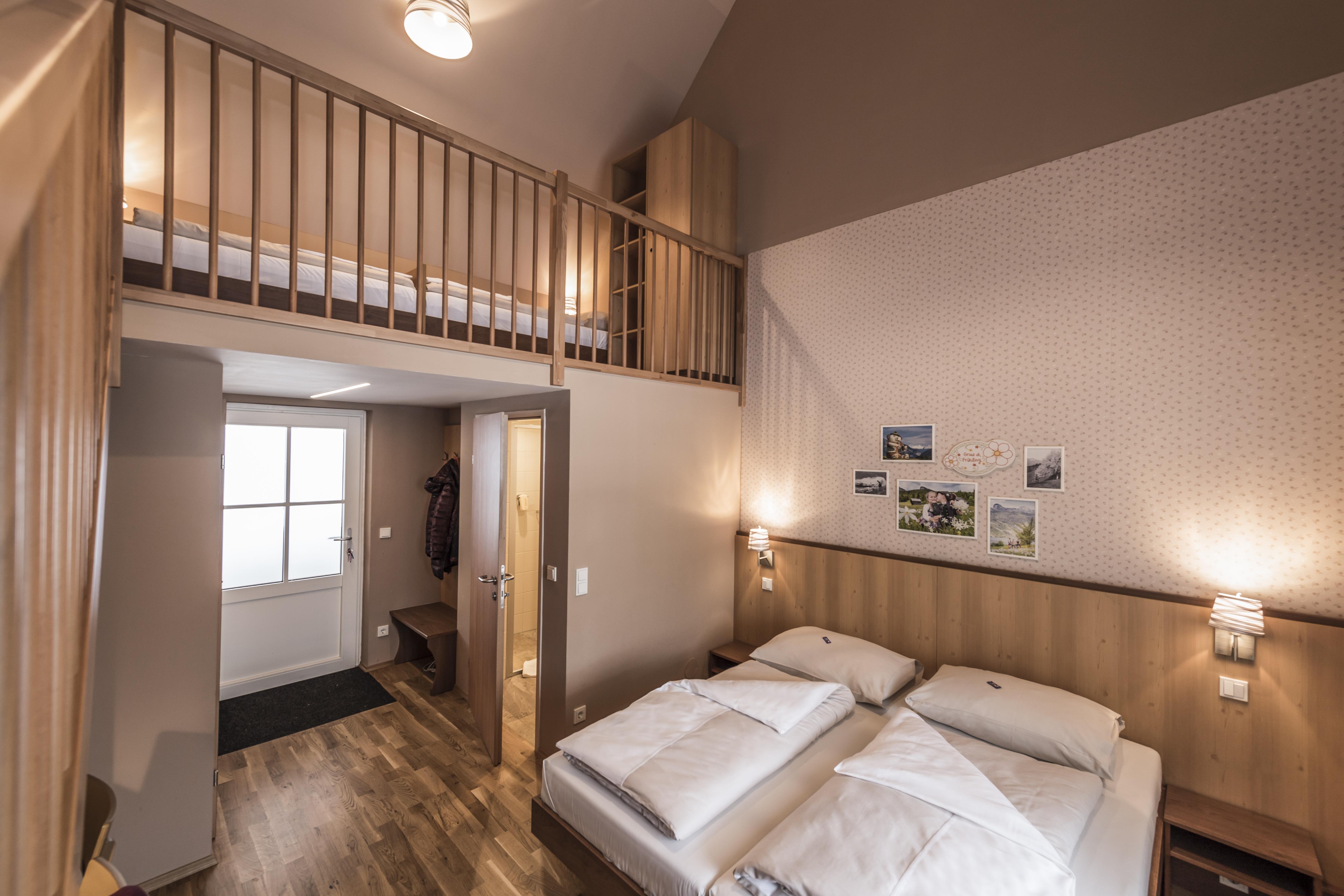 Sie sehen ein Doppelbett in einem Galeriezimmer Plus im JUFA Hotel Grundlsee*** mit Wandbildern. JUFA Hotels bietet erholsamen Familienurlaub und einen unvergesslichen Winter- und Wanderurlaub.