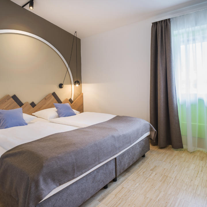 Sie sehen ein Doppelbett im Appartement 4 und 4 Plus im JUFA Hotel Wipptal. Der Ort für erholsamen Familienurlaub und einen unvergesslichen Winter- und Wanderurlaub.