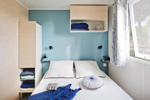 Sie sehen ein Doppelbett in einem Mobile Home beim JUFA Vulkan Thermen-Resort mit großem Fenster. JUFA Hotels bietet erholsamen Thermenspass für die ganze Familie.