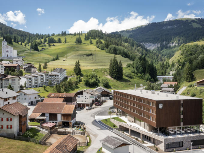 Sie sehen die Außenansicht des JUFA Hotel Savognin***s von oben mit Dorf und Berg.