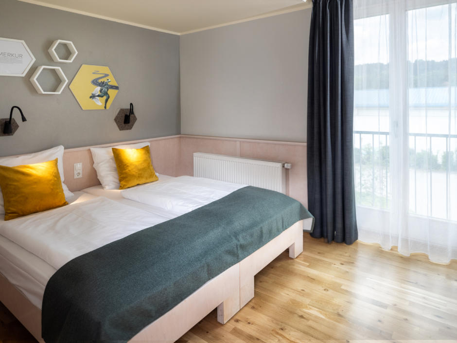 Sie sehen ein Doppelbett mit Bettlampe im JUFA Kempten. Der Ort für erholsamen Familienurlaub und einen unvergesslichen Winter- und Wanderurlaub.