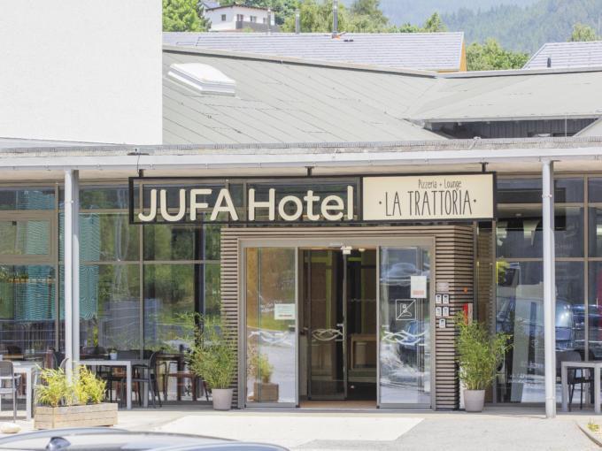Sie sehen einen Eingang zum Hotel und zur Trattoria im JUFA Hotel Wipptal. Der Ort für erholsamen Familienurlaub und einen unvergesslichen Winter- und Wanderurlaub.