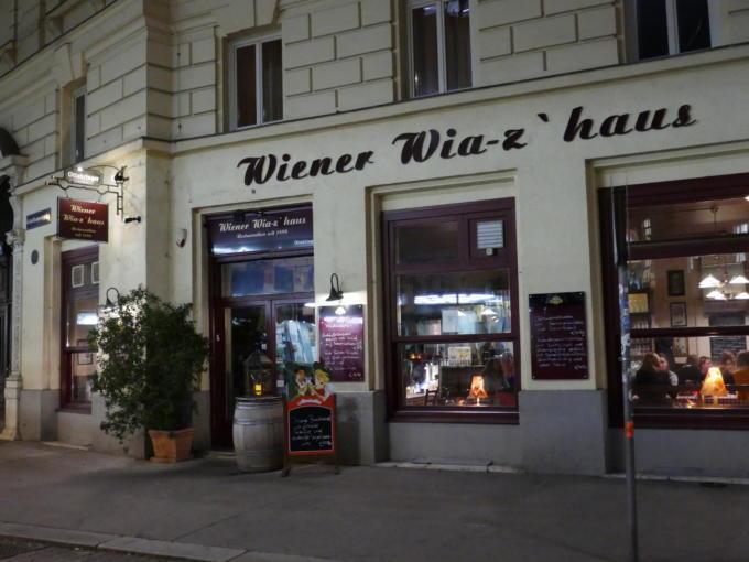 Sie sehen den Eingang eines traditionellen Wiener Wirtshauses am Abend. JUFA Hotels bietet erlebnisreichen Städtetrip für die ganze Familie und den idealen Platz für Ihr Seminar.
