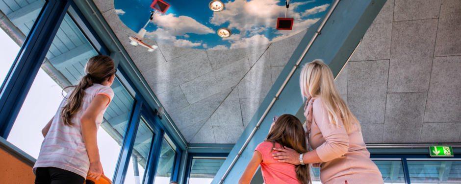Eine Familie lässt die Flugzeuge an der Decke fliegen im Energiespielpark im JUFA Hotel Jülich. JUFA Hotels bieten erholsamen Familienurlaub und einen unvergesslichen Winter- und Wanderurlaub.