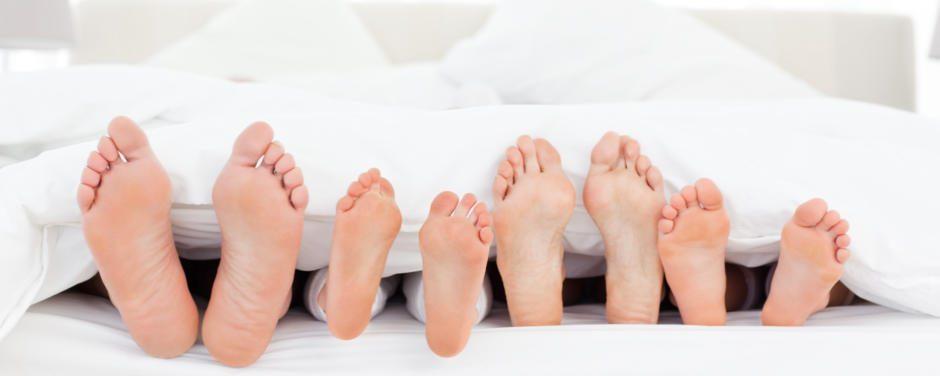 Große und kleine Füße unter weißer Bettdecke im Bett in den JUFA Hotels. Der Ort für erholsamen Familienurlaub und einen unvergesslichen Winter- und Wanderurlaub.