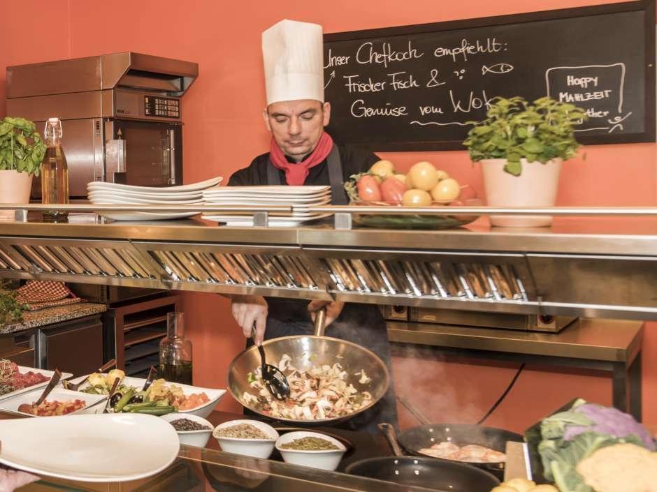 Gast beobachtet Koch bei der Ausgabe von frisch zubereiteten Speisen an der Essensausgabe im JUFA Hotel Wien City. Der Ort für erlebnisreichen Städtetrip für die ganze Familie und der ideale Platz für Ihr Seminar.