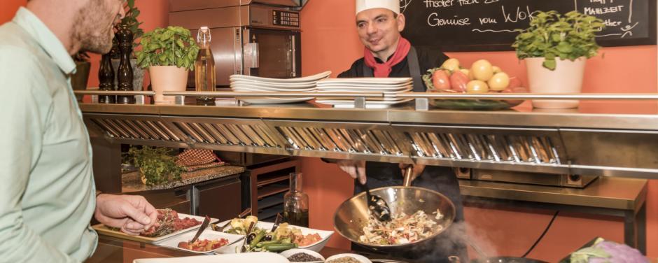 Koch und Gast bei Essensausgabe im JUFA Hotel Wien City. Der Ort für erlebnisreichen Städtetrip für die ganze Familie und der ideale Platz für Ihr Seminar.