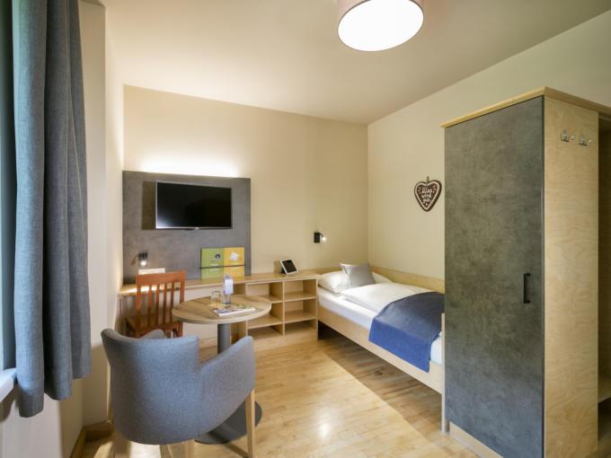Sie sehen ein Enzelzimmer des JUFA Hotels Sigmundsberg. Der Ort für erholsamen Familienurlaub und einen unvergesslichen Winter- und Wanderurlaub.