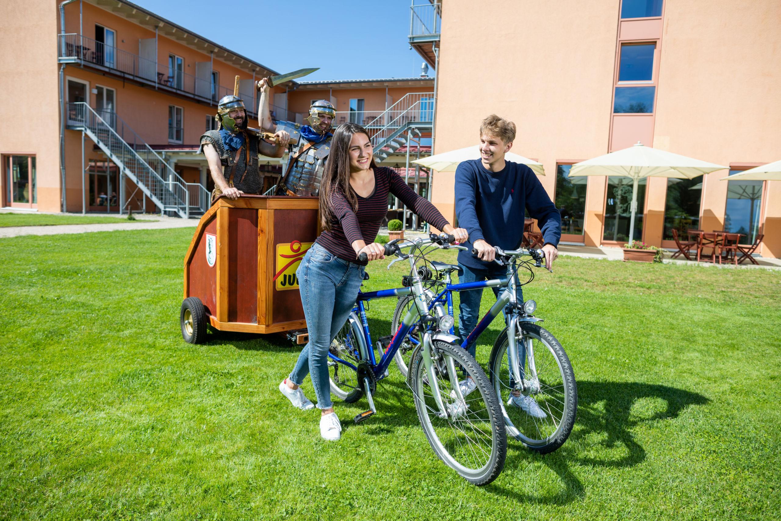 Sie sehen ein Paar mit Fahrrädern und Streitwaagen im JUFA Kempten. Der Ort für kinderfreundlichen und erlebnisreichen Urlaub für die ganze Familie.