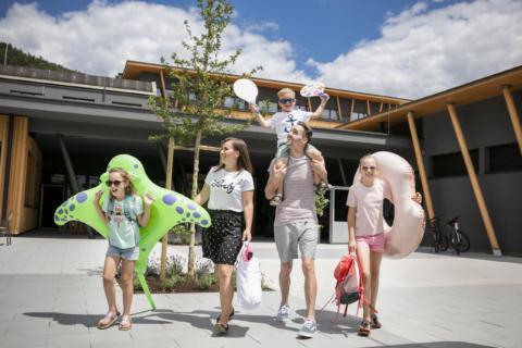 Sie sehen eine Familie am Weg zum Freibad Weiz. JUFA Hotels bietet kinderfreundlichen und erlebnisreichen Urlaub für die ganze Familie.