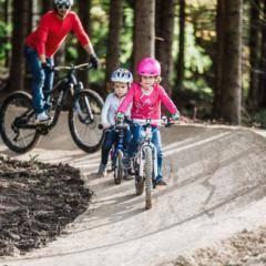 Sie sehen einen Vater mit zwei Kindern beim Mountainbiken im Mini-Bikepark beim JUFA Hotel Annaberg - Bergerlebnis-Resort. Der Ort für erholsamen Familienurlaub und einen unvergesslichen Winter- und Wanderurlaub.