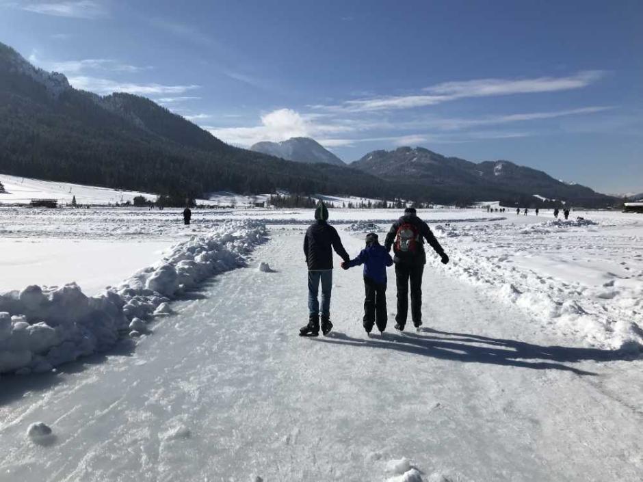 Sie sehen eine Familie beim Eislaufen auf dem Weissensee in Kärnten im Winter. JUFA Hotels bietet erholsamen Familienurlaub und einen unvergesslichen Winterurlaub.