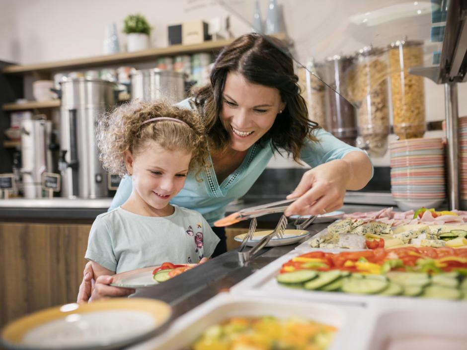 Sie sehen eine Familie am Frühstücksbuffet im JUFA Hotel Mariazell-Erlaufsee. Der Ort für erholsamen Familienurlaub und einen unvergesslichen Winter- und Wanderurlaub.