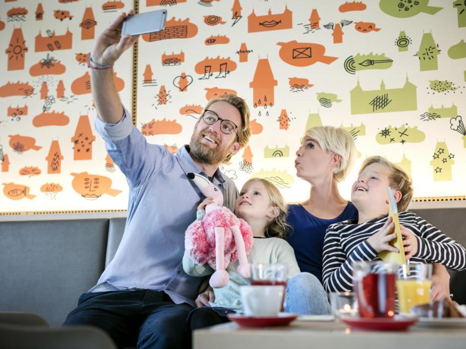 Sie sehen Famile mit Kindern ein Selfie machen im Café des JUFA Hotel Graz City***. Der Ort für erlebnisreichen Städtetrip für die ganze Familie und der ideale Platz für Ihr Seminar.