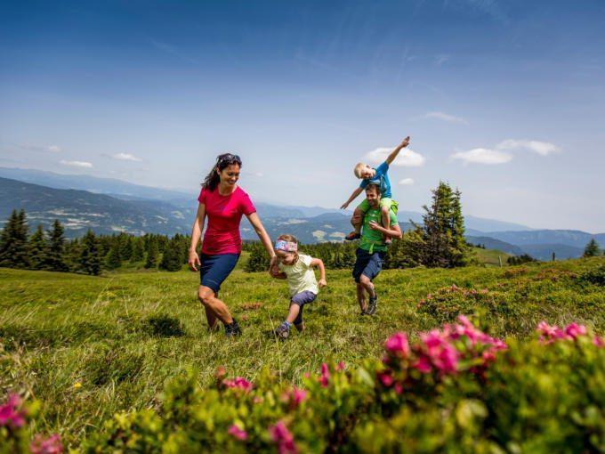Sie sehen eine Familie auf dem Kreischberg im Murtal mit Blumen im Sommer. JUFA Hotels bietet erholsamen Familienurlaub und einen unvergesslichen Winter- und Wanderurlaub.