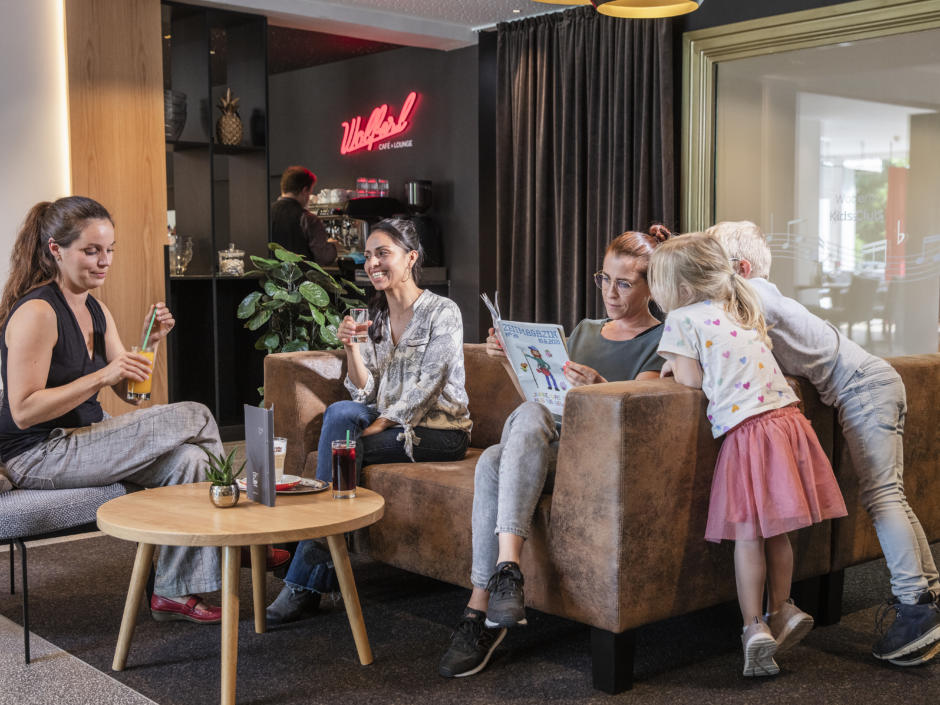 Sie sehen eine Familie mit Kindern in der Lounge im JUFA Hotel Salzburg City. Der Ort für erholsamen Familienurlaub und einen unvergesslichen Winter- und Wanderurlaub.