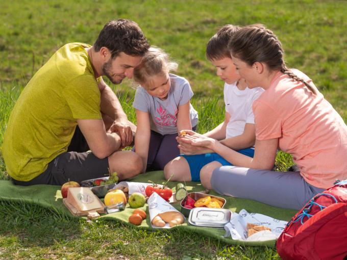 Sie sehen eine Familie beim Picknick mit einer Rauszeit-Jausenbox im Sommer. JUFA Hotels bietet erholsamen Familienurlaub und einen unvergesslichen Winter- und Wanderurlaub.