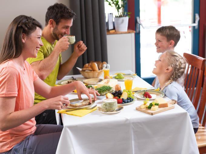 Sie sehen eine Familie beim Rauszeit-Frühstück im JUFA Hotel Maria Lankowitz. Der Ort für erholsamen Familienurlaub und einen unvergesslichen Winter- und Wanderurlaub.