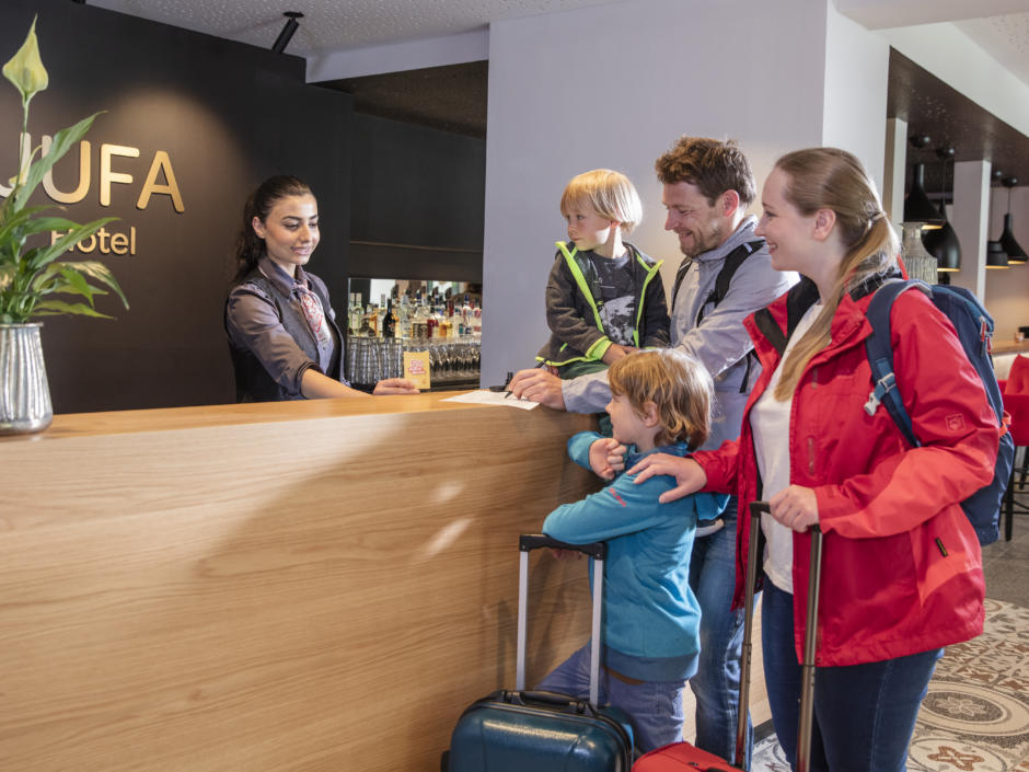 Sie sehen eine Familie an der Rezeption im JUFA Hotel Salzburg City. Der Ort für erholsamen Familienurlaub und einen unvergesslichen Winter- und Wanderurlaub.