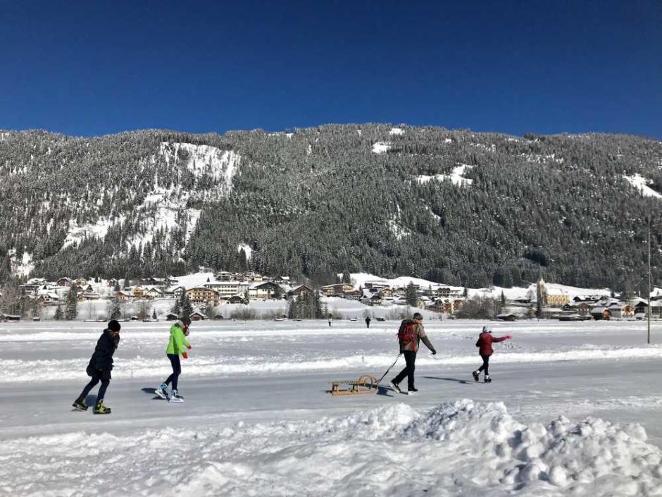 Sie sehen eine Familie mit einem Schlitten auf dem Weissensee in Kärnten im Winter. JUFA Hotels bietet erholsamen Familienurlaub und einen unvergesslichen Winterurlaub.