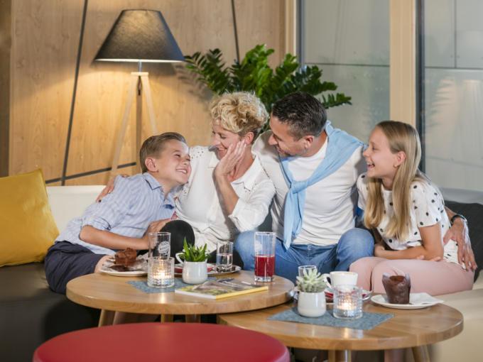 Sie sehen eine Familie in der Sitzecke im JUFA Hotel Weiz. Der Ort für kinderfreundlichen und erlebnisreichen Urlaub für die ganze Familie.