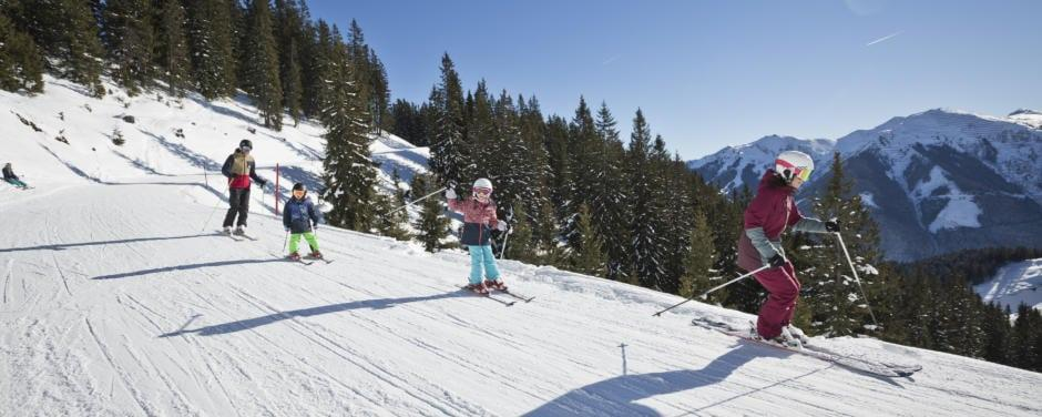 Sie sehen eine Familie bei einer Skiabfahrt im Skicircus Saalbach Hinterklemm. JUFA Hotels bietet erholsamen Familienurlaub und einen unvergesslichen Winterurlaub.