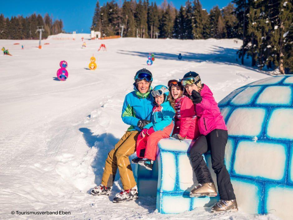 Sie sehen eine Familie beim Skifahren auf dem Monte Popolo mit einem Iglu. JUFA Hotels bietet erholsamen Familienurlaub und einen unvergesslichen Winterurlaub.
