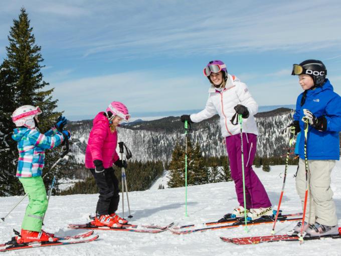 Sie sehen eine Familie beim Skifahren im Skigebiet Annaberg. JUFA Hotels bietet erholsamen Familienurlaub und einen unvergesslichen Winterurlaub.