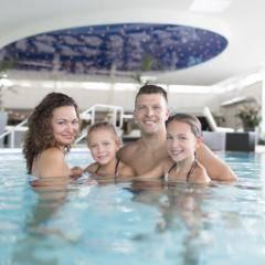 Sie sehen eine Familie in der Solymar Therme in Bad Mergentheim. JUFA Hotels bietet erholsamen Familienurlaub und einen unvergesslichen Winter- und Wanderurlaub.