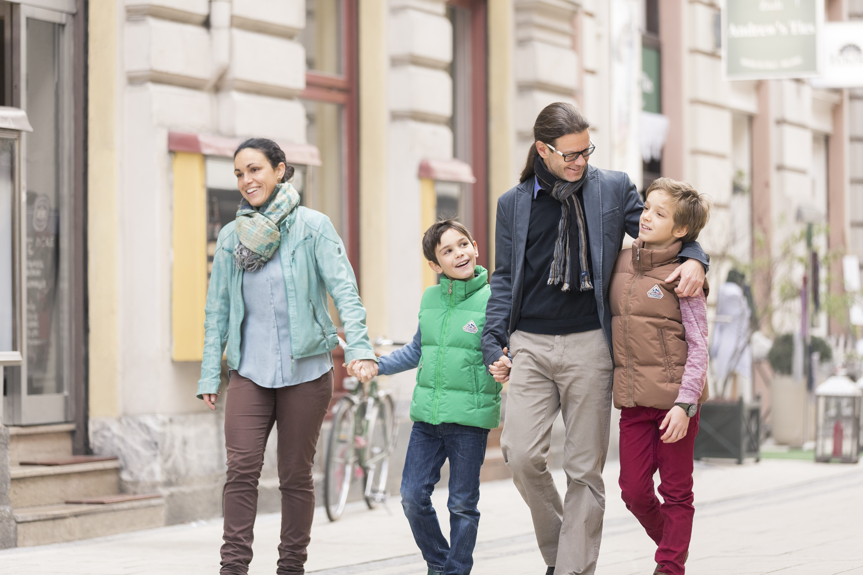 Familie spaziert durch die Fußgängerzone in Graz in der Nähe von JUFA Hotels. Der Ort für erlebnisreichen Städtetrip für die ganze Familie und der ideale Platz für Ihr Seminar.